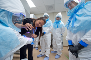 UC Irvine's BSL-3 biosafety training program instructor Tran B. Phan inspects a student for contamination under UV light during a spill simulation. Steve Zylius / UC Irvine